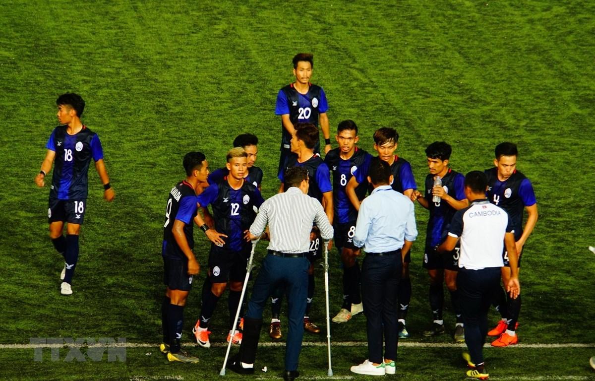 Huấn luyện viên U22 Campuchia (chống nạng) chỉ đạo các cầu thủ. (Ảnh: TTXVN)