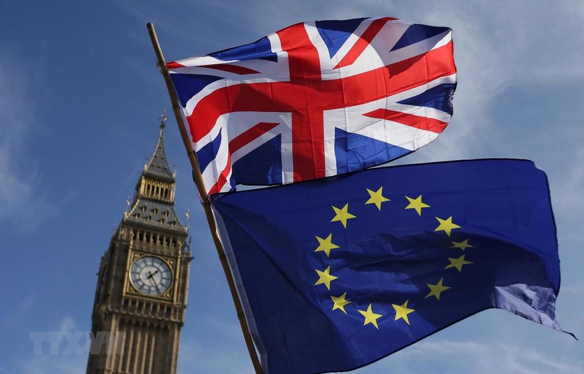 Quốc kỳ Anh (phía trên) và cờ Liên minh châu Âu (EU) phía dưới bên ngoài tòa nhà Quốc hội Anh ở London. (Ảnh: AFP/TTXVN)
