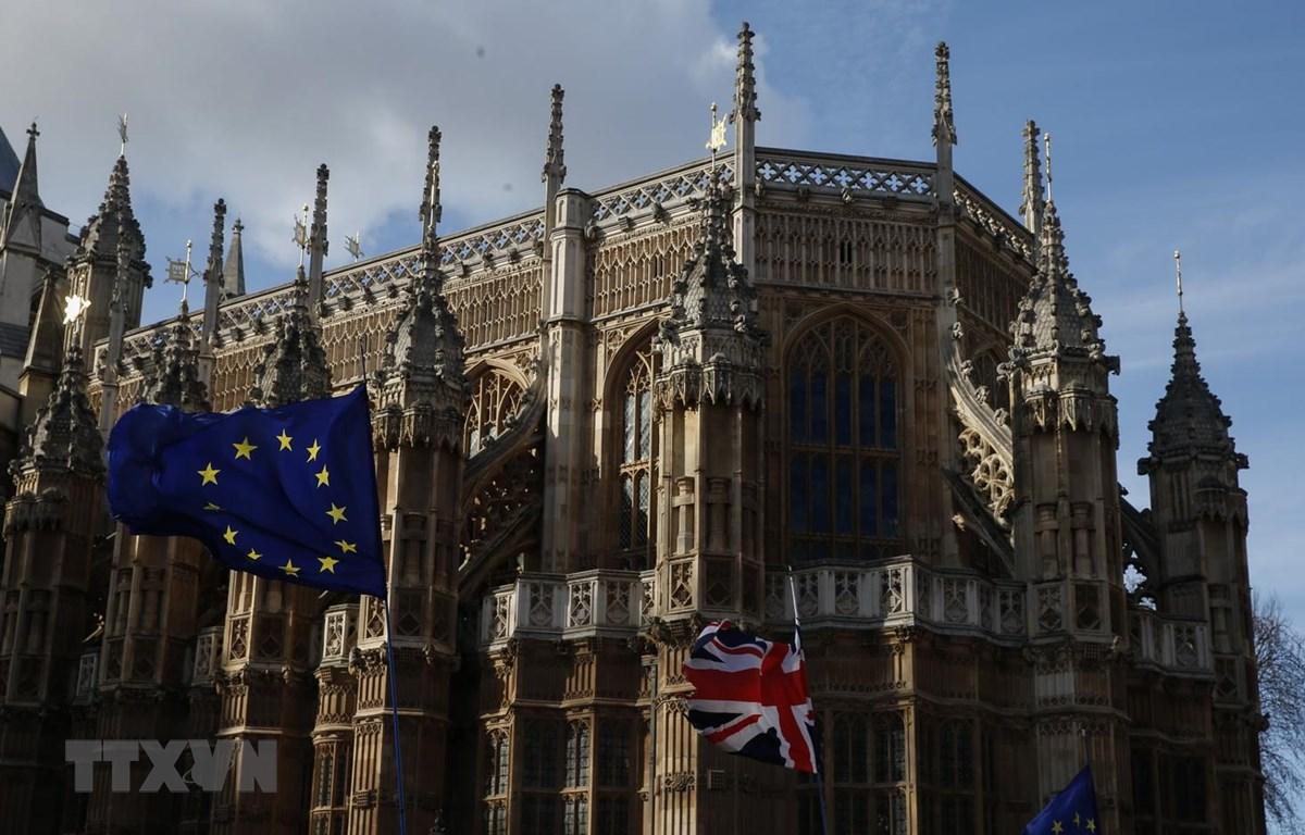 Cờ Anh (phải) và cờ EU (trái) tại London, ngày 14/3. (Ảnh: THX/ TTXVN)