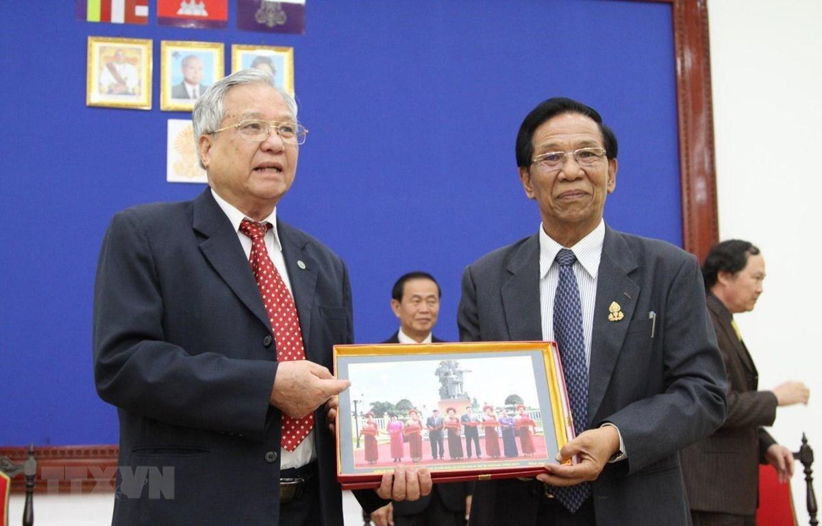 Đại tá Trịnh Vinh Pha, Phó chủ tịch Trung ương Hội hữu nghị Việt Nam-Campuchia (trái) và Phó chủ tịch thứ nhất Thượng viện Campuchia Sim Ka cùng trao quà lưu niệm. (Ảnh: TTXVN)