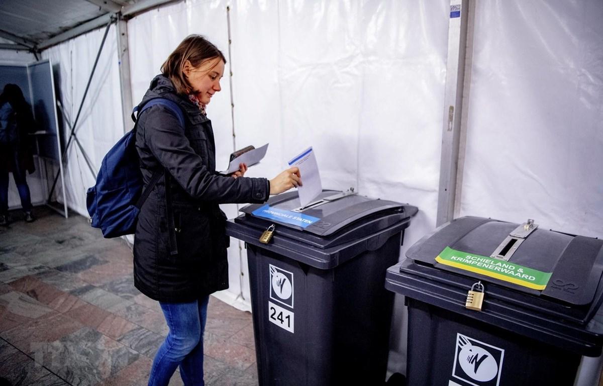 Cử tri bỏ phiếu trong cuộc bầu cử địa phương tại một điểm bầu cử ở Rotterdam, Hà Lan. (Ảnh: AFP/TTXVN)