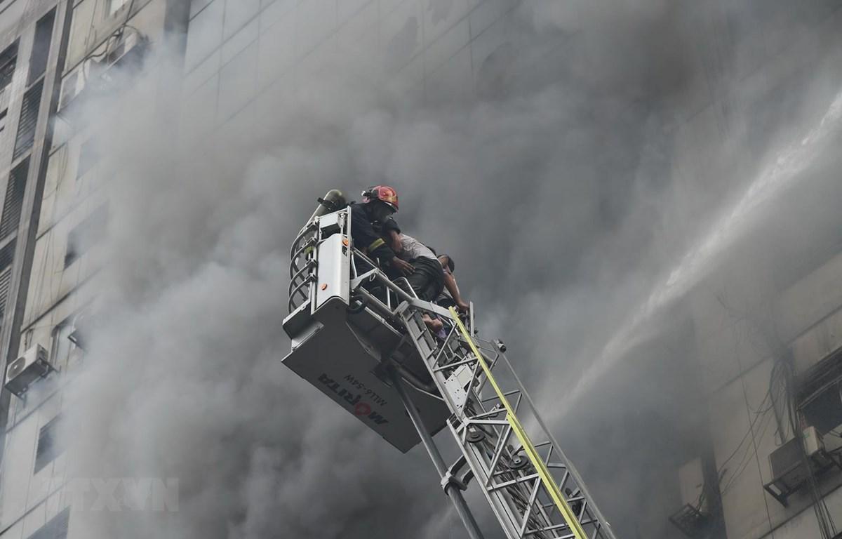Lực lượng cứu hỏa nỗ lực dập lửa tại hiện trường vụ cháy tòa nhà thương mại 22 tầng ở Dhaka, Bangladesh. (Ảnh: THX/TTXVN)