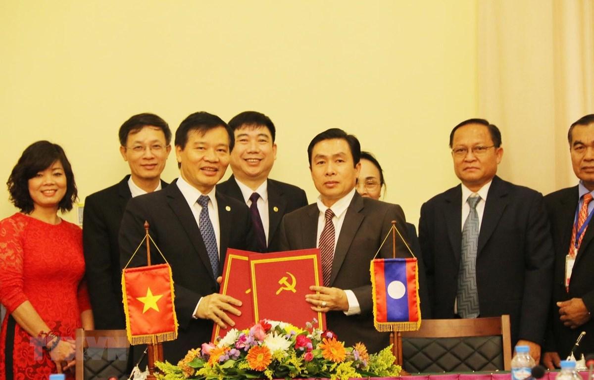 Phó Chánh Văn phòng Trung ương Đảng Cộng sản Việt Nam Bùi Văn Thạch (trái) và Phó Chánh Văn phòng Trung ương Đảng Nhân dân cách mạng Lào Khampha Phimmasone ký Biên bản bàn giao. (Ảnh: Xuân Tú/TTVXN)