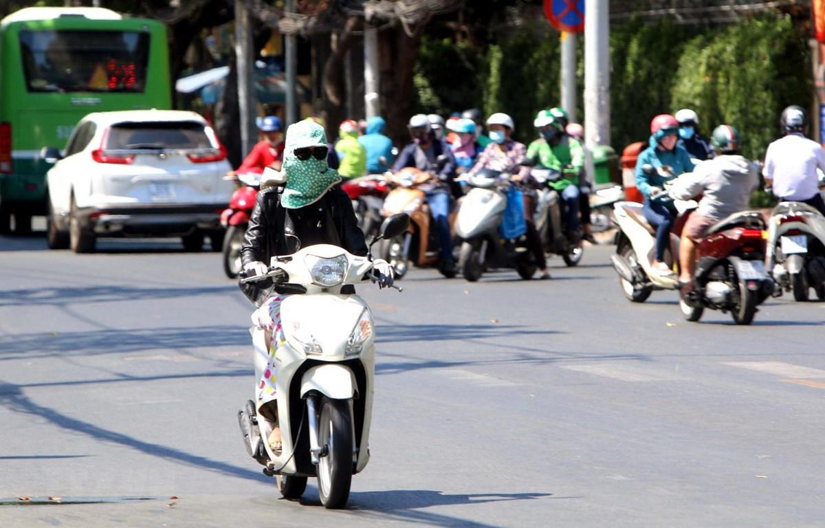 Người dân Thành phố Hồ Chí Minh trùm kín người khi đi ra đường. (Ảnh: Thanh Vũ/TTXVN)