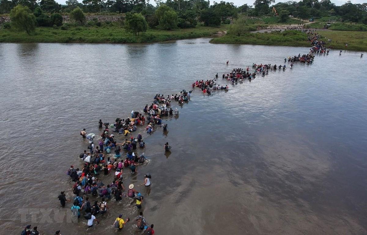 Người di cư băng qua sông Suchiate để tới Mexico, trong hành trình tới Mỹ, ngày 2/11/2018. (Ảnh: AFP/TTXVN)
