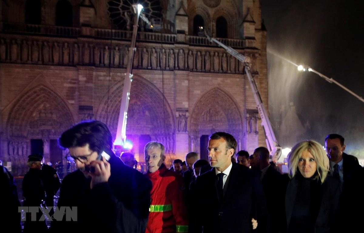 Tổng thống Pháp Emmanuel Macron cùng phu nhân thị sát hiện trường vụ cháy Nhà thờ Đức Bà ở Paris tối 15/4/2019. (Ảnh: AFP/TTXVN)