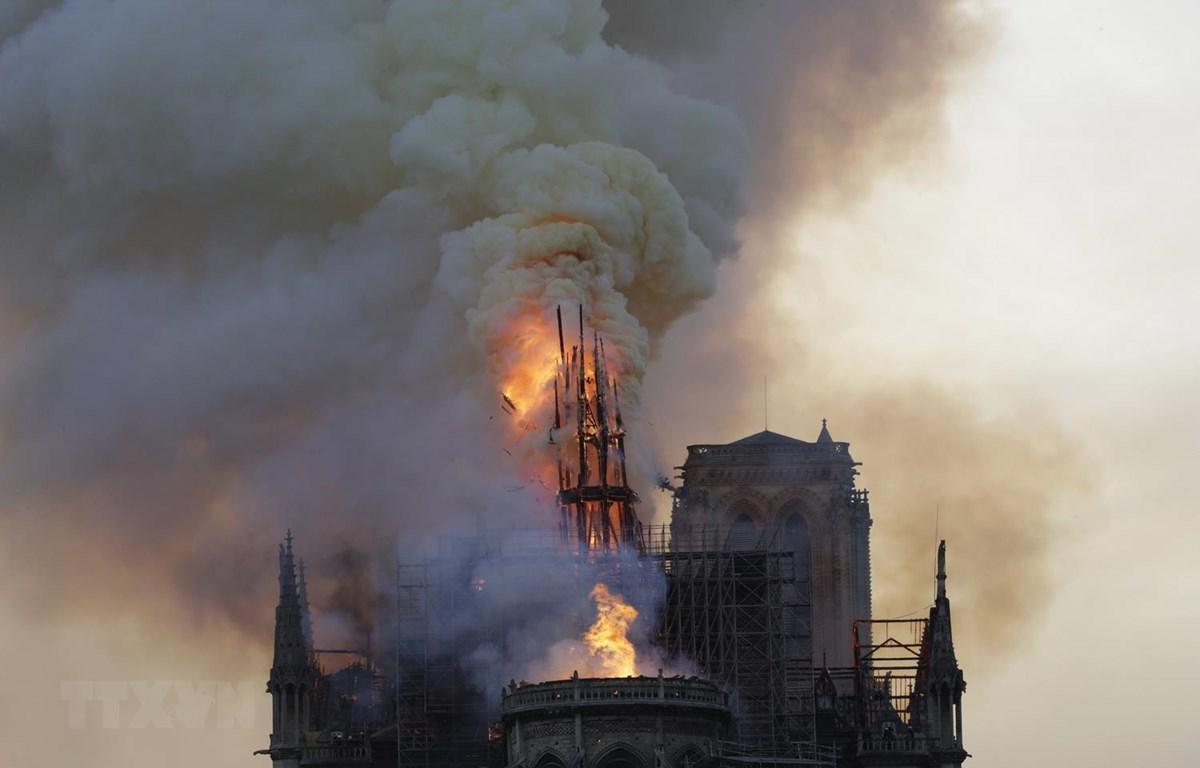 Tháp chuông bị sập khi lửa khói bao trùm nóc Nhà thờ Đức Bà ở Paris, Pháp. (Ảnh: AFP/TTXVN)