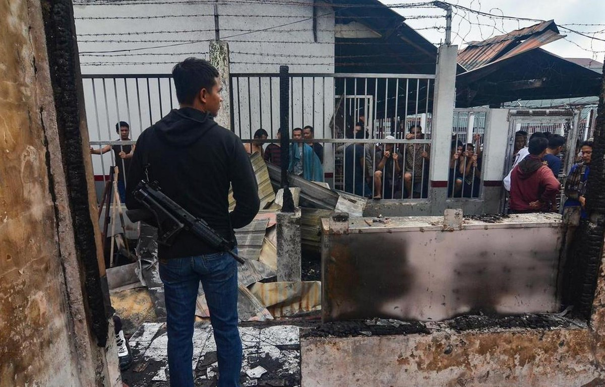 Một cảnh sát bảo vệ khu vực nhà tù ở khu vực Siak sau khi xảy ra vụ đốt trại giam. (Nguồn: AFP)