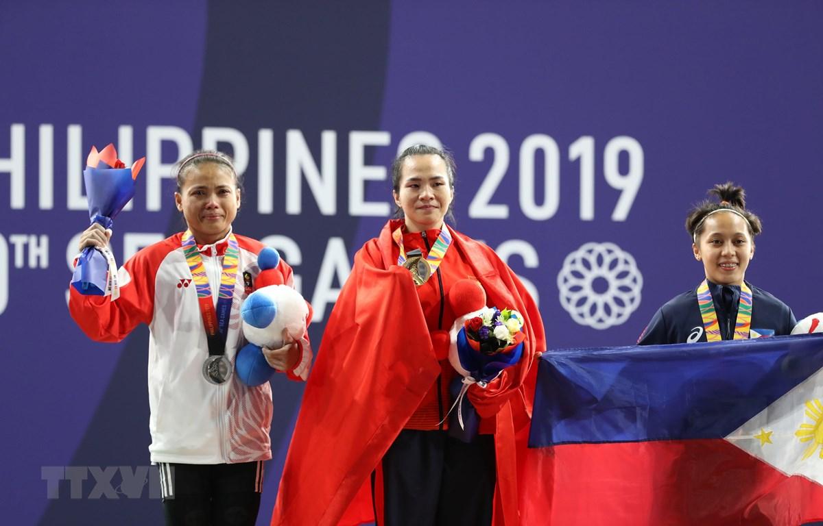 Vương Thị Huyền (giữa) trên bục nhận huy chương vàng nội dung cử tạ 45kg nữ. (Ảnh Hoàng Linh/TTXVN)