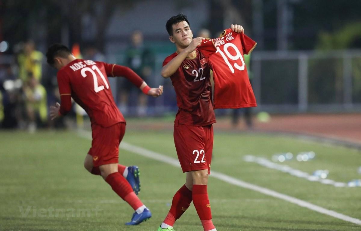 Tiến Linh, người hùng của U22 Việt Nam giơ cao chiếc áo của Quang Hải. (Ảnh: Vietnam+)