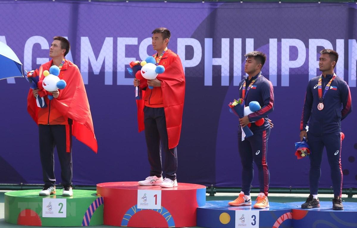 Daniel Cao Nguyễn (trái) và Lý Hoàng Nam (thứ 2 từ trái qua) thực hiện nghii thức chào cờ tại lễ trao giải. (Ảnh: Hoàng Linh/TTXVN)