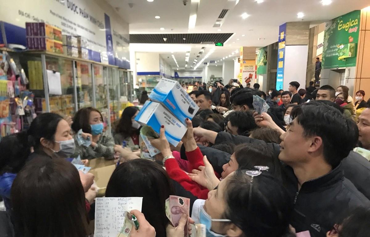 Người dân chen lấn, tranh nhau mua khẩu trang tại chợ thuốc Hapulico, Thanh Xuân, Hà Nội. (Ảnh: Sơn Bách/Vietnam+)
