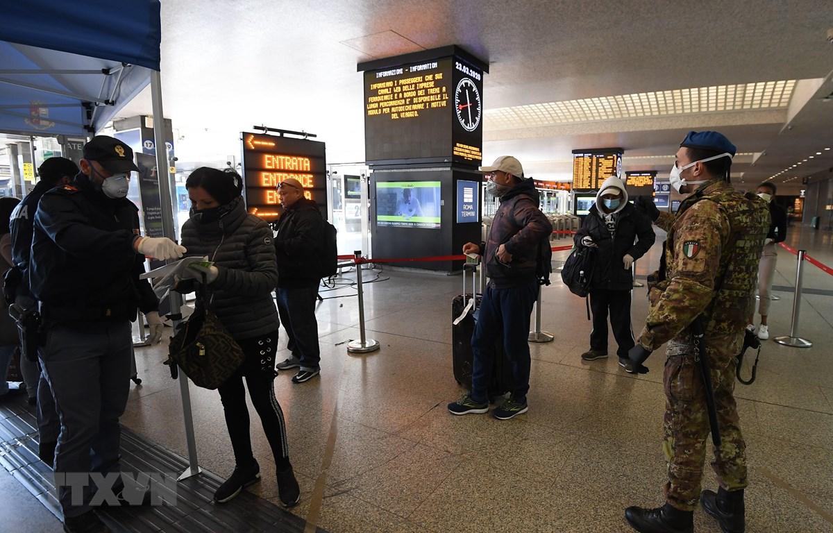 Cảnh sát kiểm tra giấy tờ của hành khách tại nhà ga tàu hỏa Roma Termini ở Rome, Italy ngày 23/3/2020, trong bối cảnh dịch COVID-19 lan rộng. (Ảnh: THX/TTXVN)