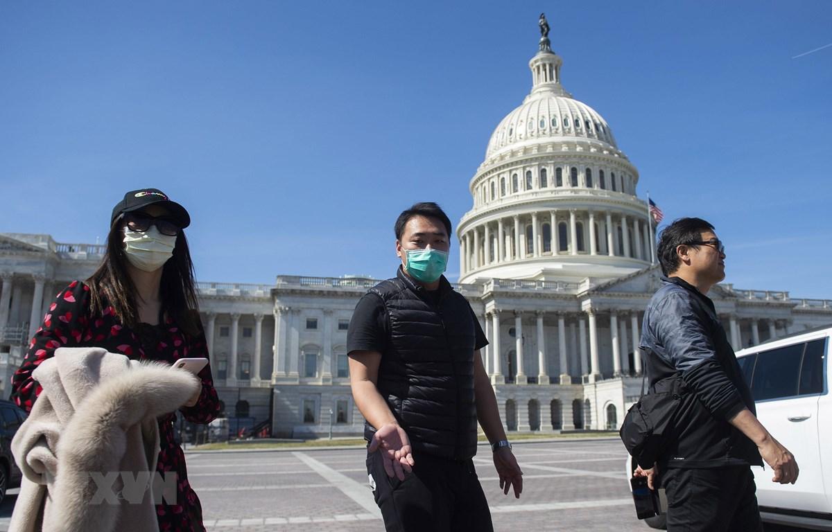 Người dân đeo khẩu trang để phòng tránh lây nhiễm COVID-19, bên ngoài tòa nhà Quốc hội Mỹ ở Washington, DC, ngày 9/3/2020. (Ảnh: AFP/TTXVN)