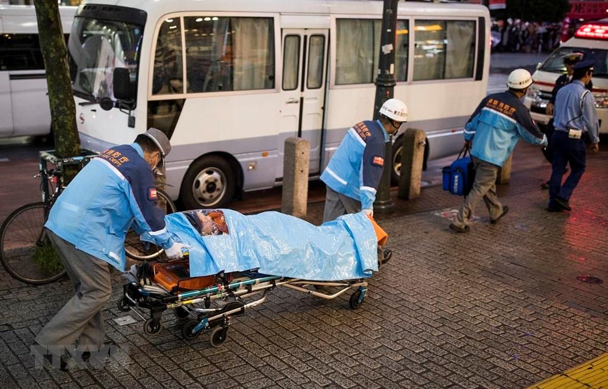Nhân viên y tế chuyển bệnh nhân bị nghi mắc COVID-19 tại quận Shibuya, Tokyo, Nhật Bản. (Ảnh: AFP/TTXVN)