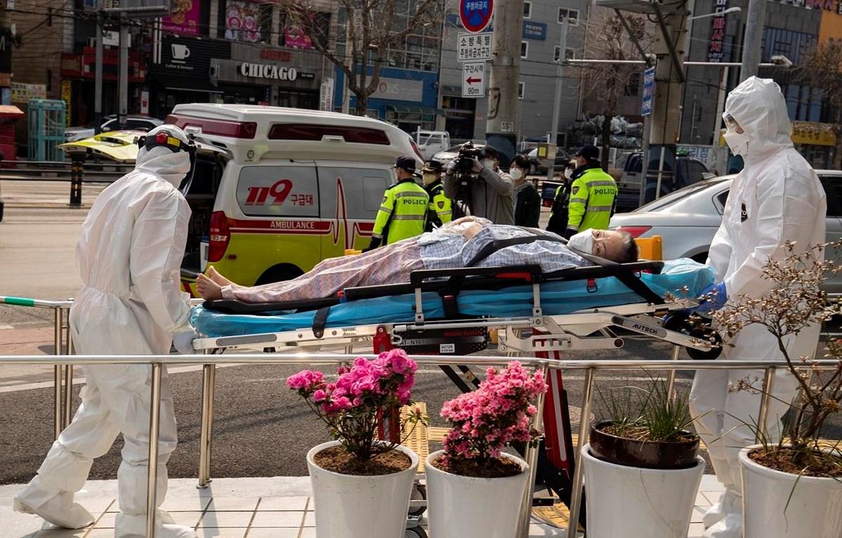 Nhân viên y tế chuyển bệnh nhân nhiễm COVID-19 tới điều trị tại bệnh viện ở Daegu, Hàn Quốc ngày 19/3/2020. (Ảnh: THX/TTXVN)
