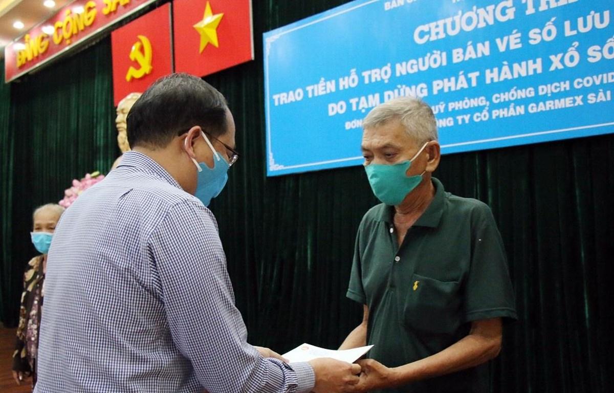 Chủ tịch UBND huyện Hóc Môn trao tiền hỗ trợ cho người bán vé số trên địa bàn. (Ảnh: Tiến Lực/TTXVN)
