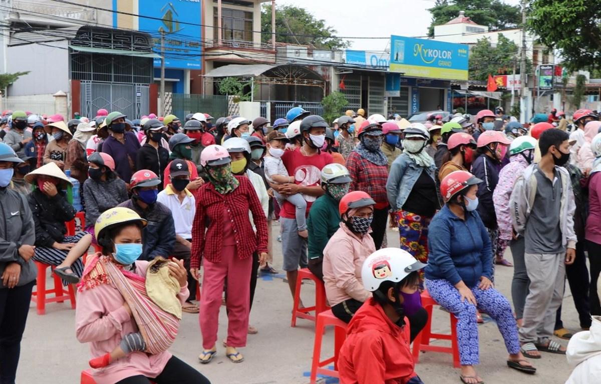Người dân tụ tập đông người bên ngoài để chờ nhận gạo. (Ảnh: Cao Nguyên/TTXVN)