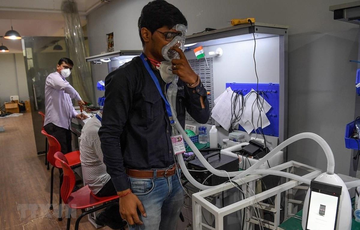 Nhân viên giới thiệu cách sử dụng máy trợ thở cầm tay. (Ảnh: AFP/TTXVN)