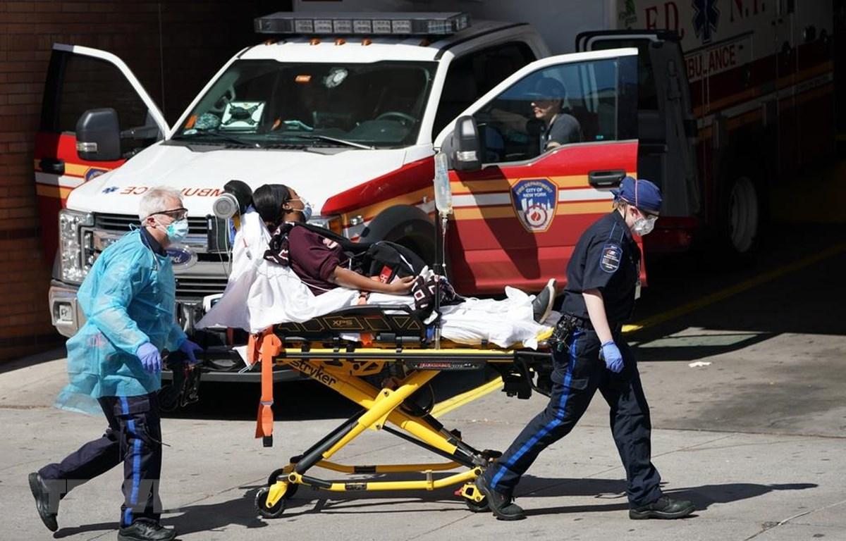 Nhân viên y tế chuyển bệnh nhân mắc COVID-19 từ xe cứu thương vào một bệnh viện ở New York, Mỹ ngày 6/4/2020. (Ảnh: AFP/TTXVN)