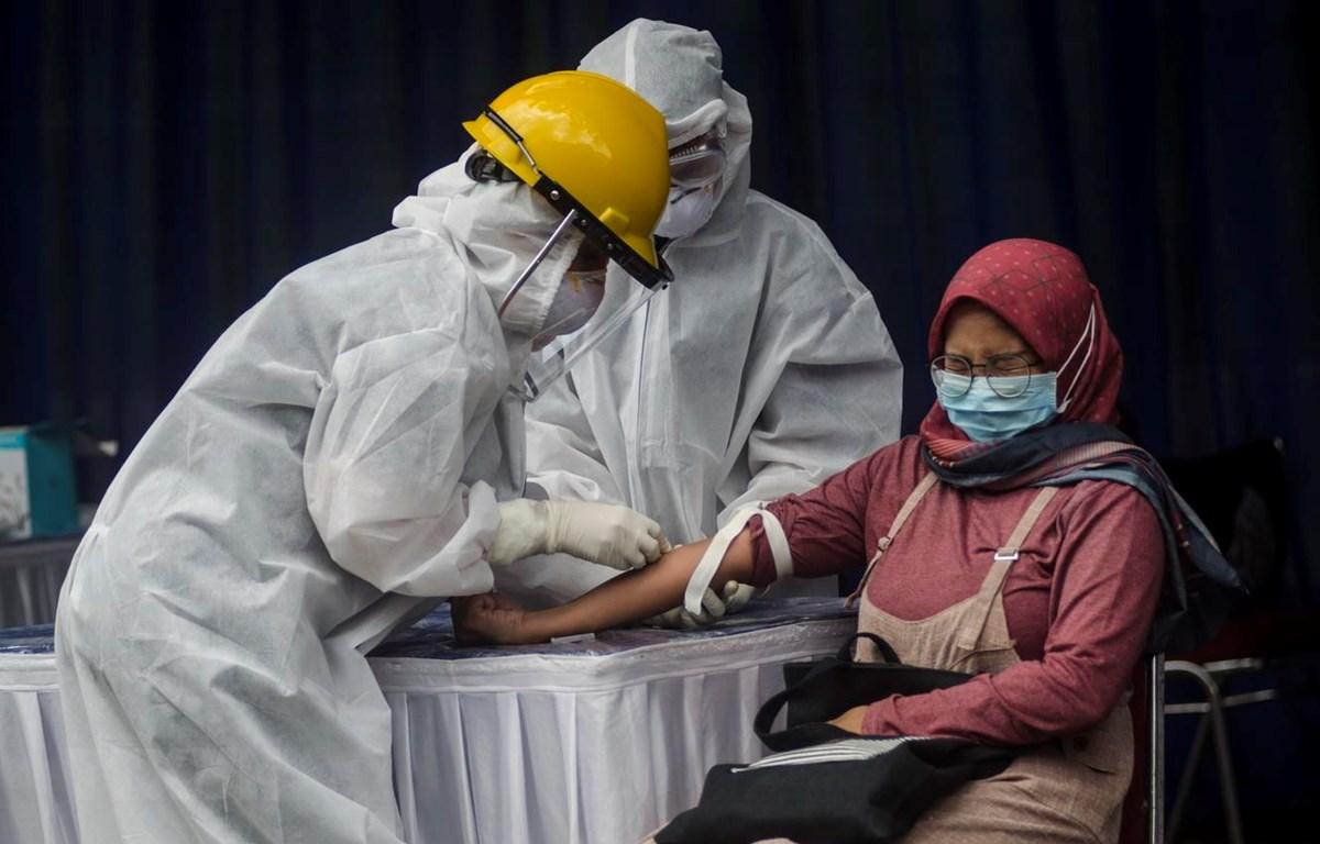 Nhân viên y tế lấy mẫu xét nghiệm COVID-19 cho người dân tại tỉnh Tây Java, Indonesia ngày 4/4/2020. (Ảnh: THX/TTXVN)