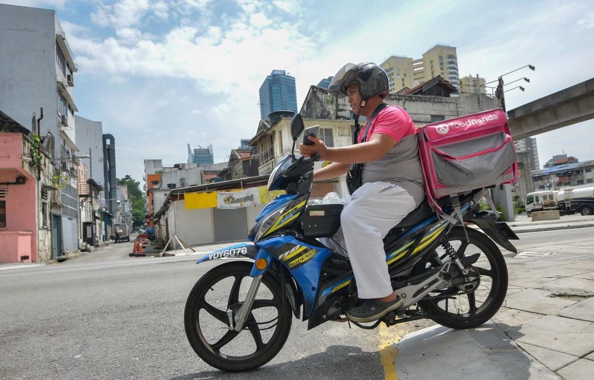 Nhân viên giao đồ ăn tại Kuala Lumpur, Malaysia ngày 19/3/2020. (Ảnh: THX/TTXVN)