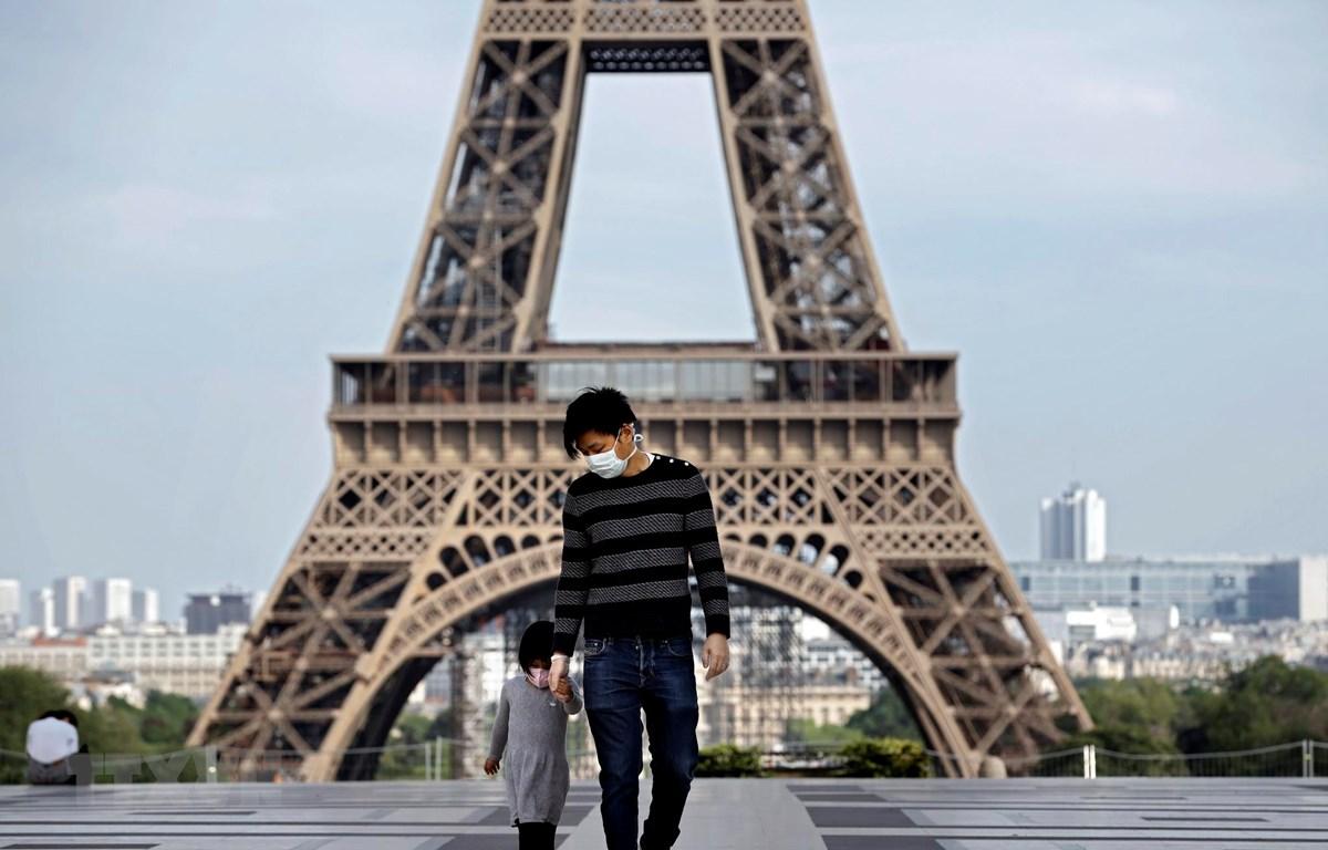 Trẻ em thăm Tháp Eiffel ở Paris, Pháp trong bối cảnh dịch COVID-19 bùng phát mạnh, ngày 20/4/2020. (Ảnh: AFP/TTXVN)
