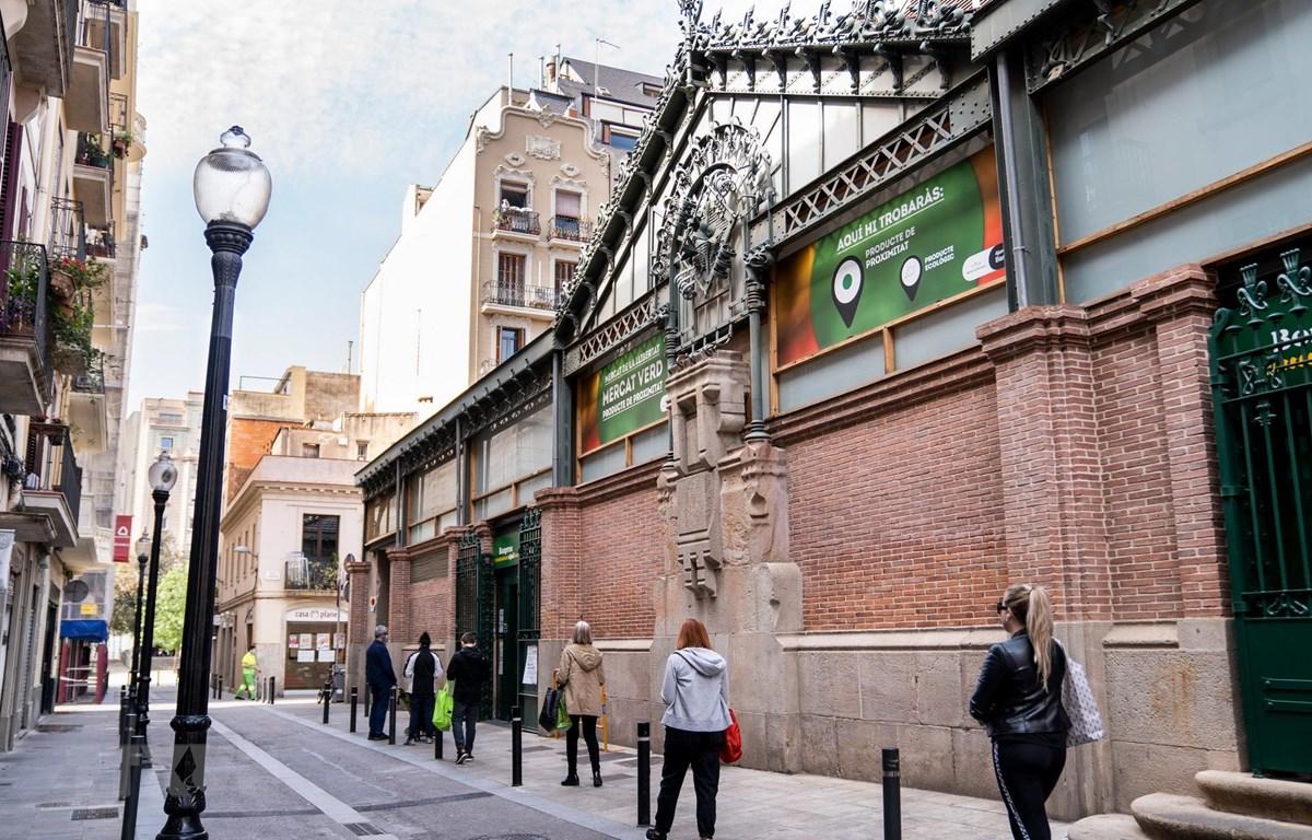Người dân thực hiện giãn cách xã hội để phòng lây nhiễm COVID-19 khi xếp hàng bên ngoài một khu chợ ở Barcelona, Tây Ban Nha ngày 8/5/2020. (Ảnh: THX/TTXVN)