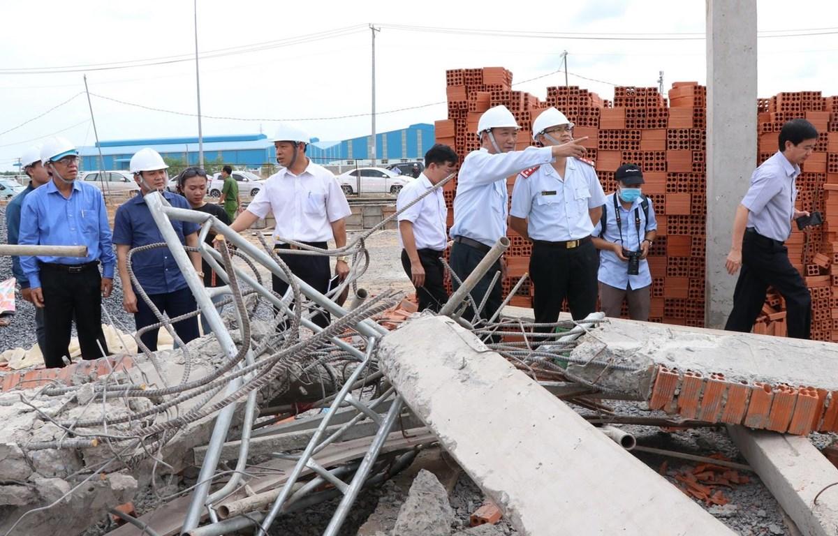 Thứ trưởng Lê Quang Hùng cùng đoàn công tác liên bộ kiểm tra hiện trường sập công trình xây dựng. (Ảnh: Sỹ Tuyên/TTXVN)