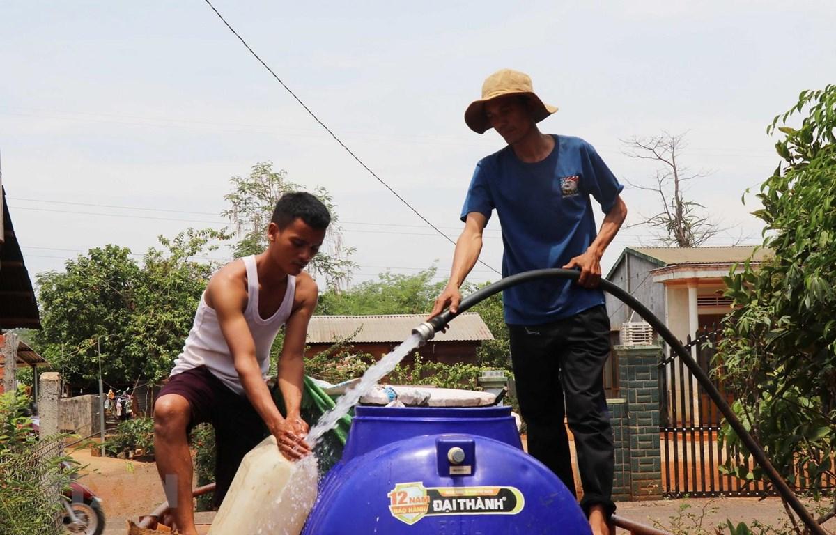 Người dân xã Ea Nuôi, huyện Buôn Đôn phải đi xin nước về phục vụ cho sinh hoạt. (Ảnh: Tuấn Anh/TTXVN)