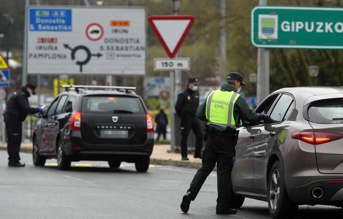 Lực lượng dân phòng Tây Ban Nha kiểm tra các phương tiện tại một trạm kiểm soát biên giới. (Ảnh: AFP/TTXVN)