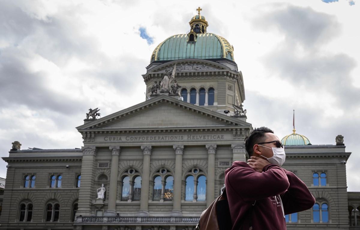 Du khách đeo khẩu trang đi ngang qua Tòa nhà Quốc hội Thụy Sĩ. (Nguồn: AFP)