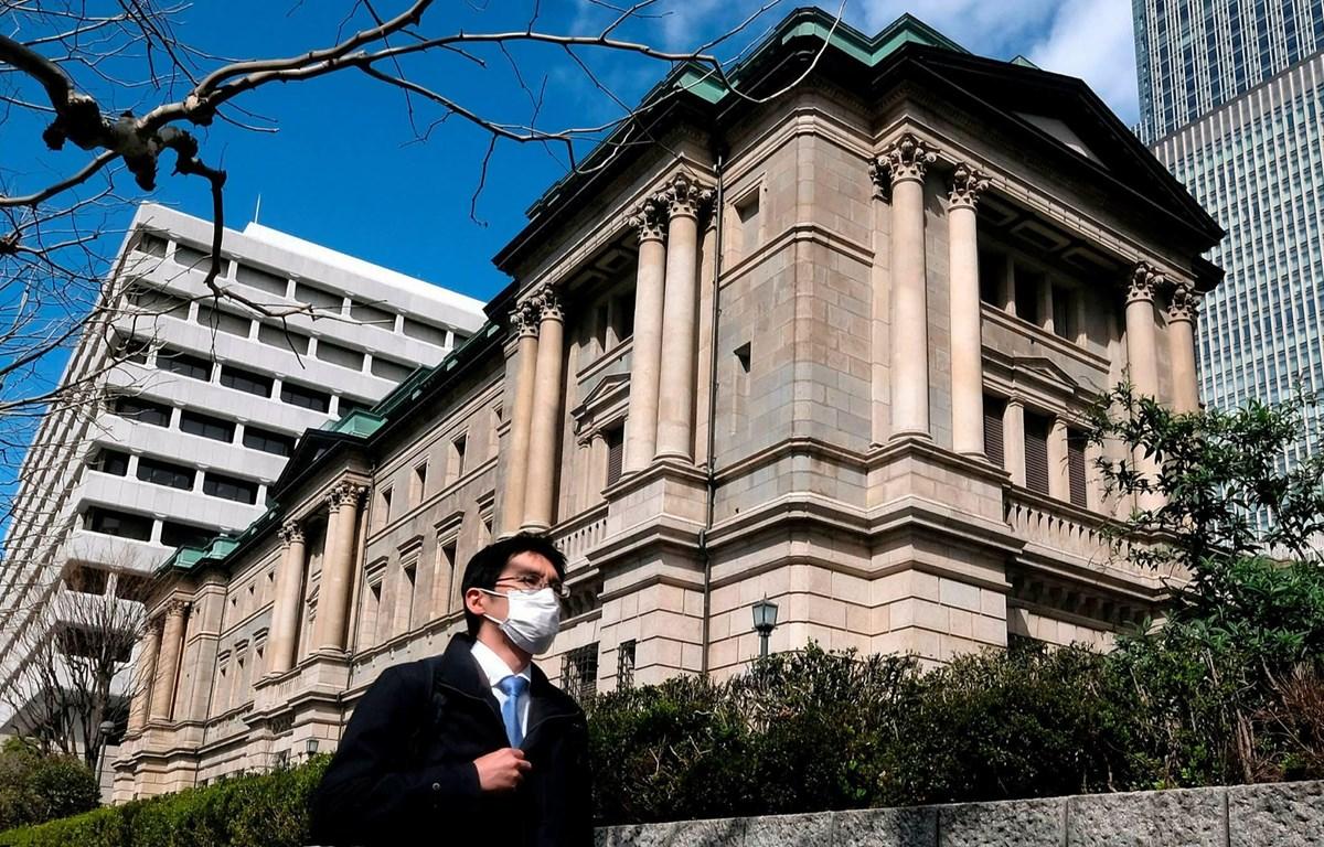 Người dân đeo khẩu trang phòng dịch COVID-19 đi ngang qua trụ sở Ngân hàng Trung ương Nhật Bản. (Nguồn: AFP)