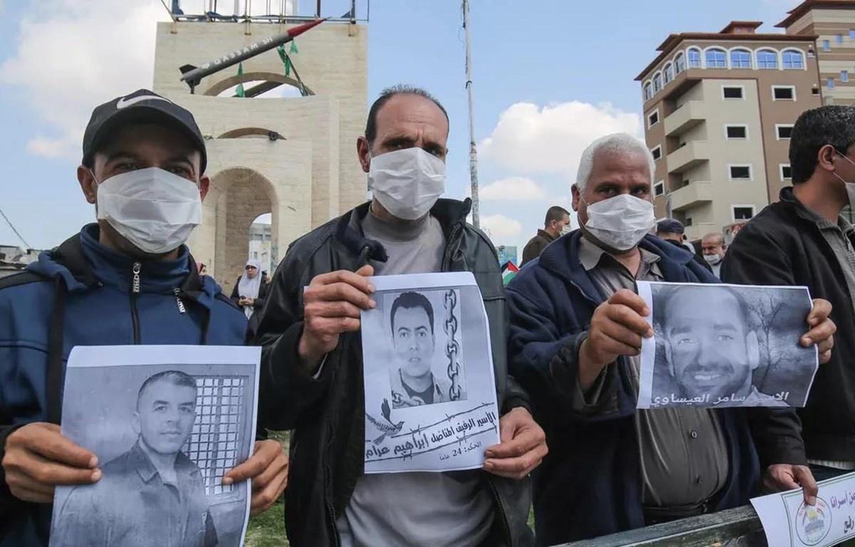 Người dân Palestine cầm bức ảnh của các tù nhân bị Israel bắt giữ. (Nguồn: AFP)