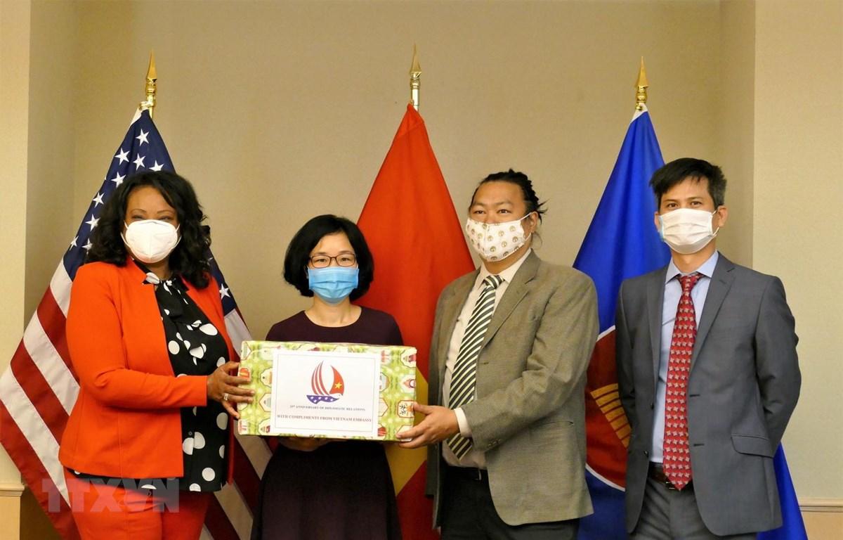 Tham tán Công sứ Hoàng Thị Thanh Nga trao tặng khẩu trang cho đại diện chính quyền Thủ đô Washington. (Ảnh: PV TTXVN tại Mỹ)