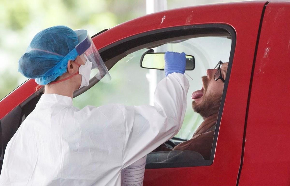 Nhân viên y tế lấy mẫu dịch xét nghiệm COVID-19 cho người dân tại Washington D.C., Mỹ, ngày 19/5/2020. (Ảnh: THX/TTXVN)