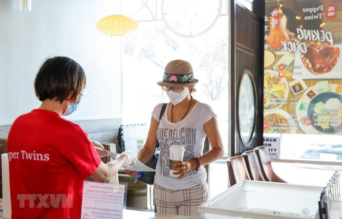 Người dân đeo khẩu trang phòng lây nhiễm COVID-19 tại một nhà hàng ở Houston, Texas, Mỹ, ngày 2/7/2020. (Ảnh: THX/TTXVN)