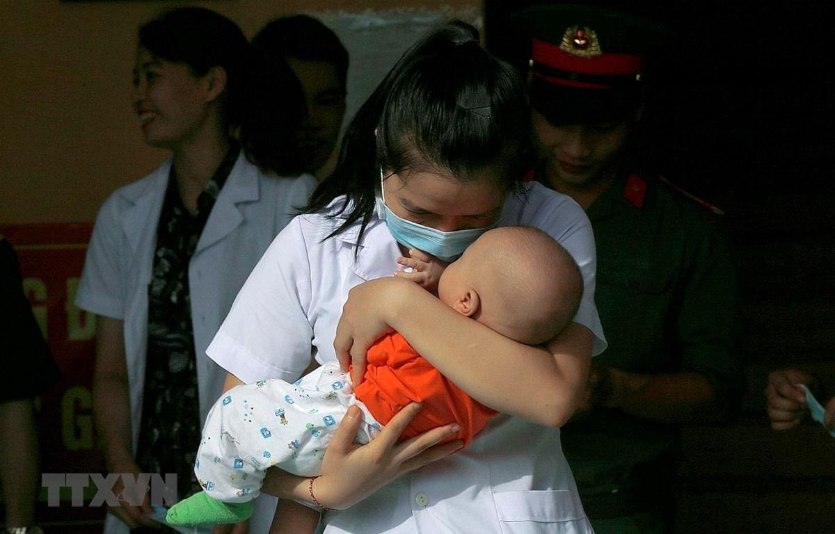 Bác sỹ Bùi Thị Liệu, cán bộ Trung tâm xét nghiệm CDC tỉnh Hòa Bình xúc động chia tay bé Trường An (Hà Tĩnh) 5 tháng tuổi trong ngày hoàn thành cách ly. (Ảnh: Trọng Đạt/TTXVN)