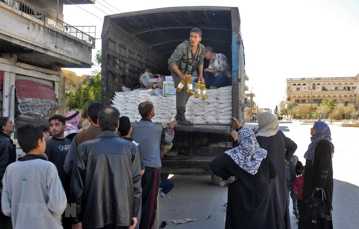 Người dân xếp hàng nhận nhu yếu phẩm cứu trợ tại Al-Qaryatain, Syria. (Ảnh: AFP/TTXVN)