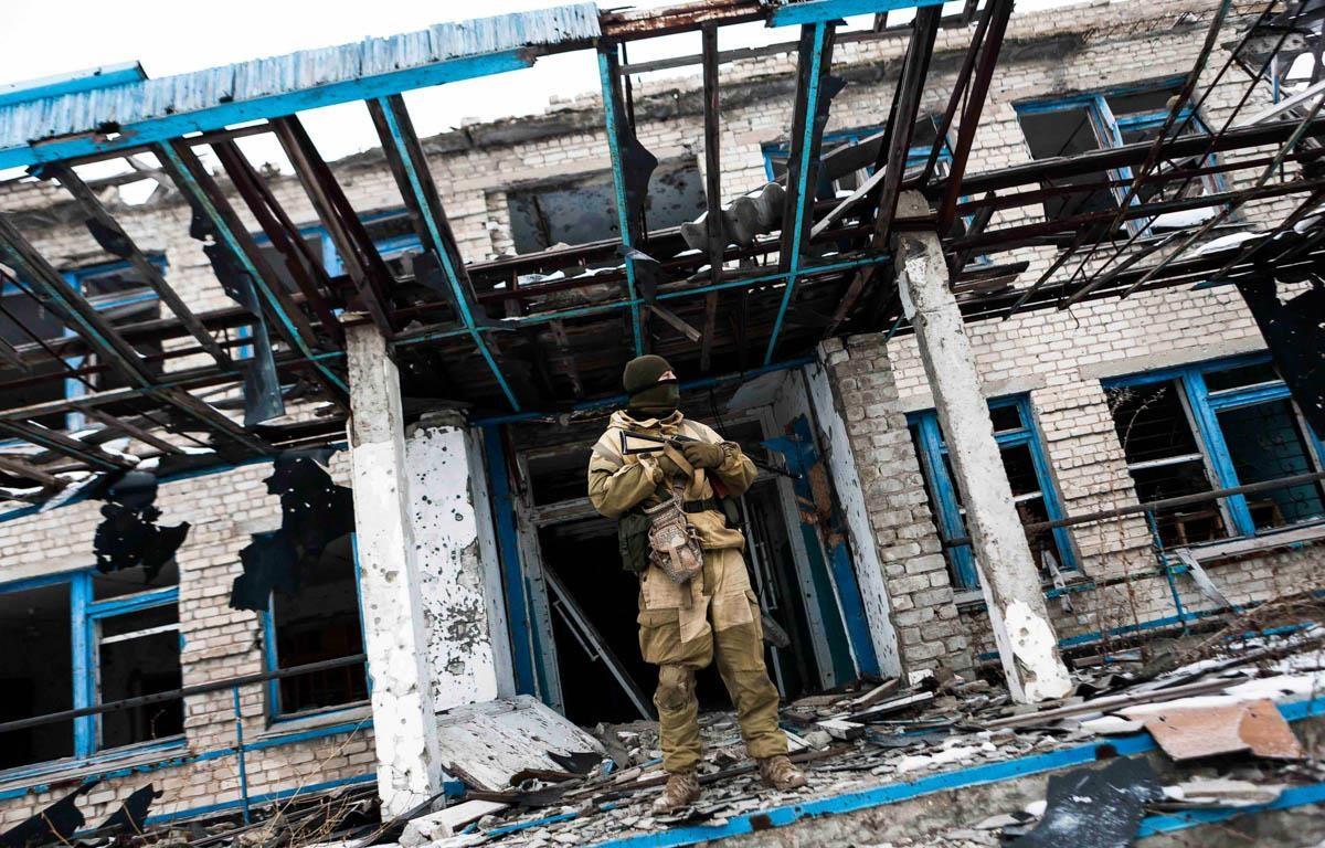 Binh sỹ Ukraine đứng trước một ngôi trường bị phá hủy tại thành phố Mariupol thuộc tỉnh Donetsk. (Nguồn: Aljazeera)