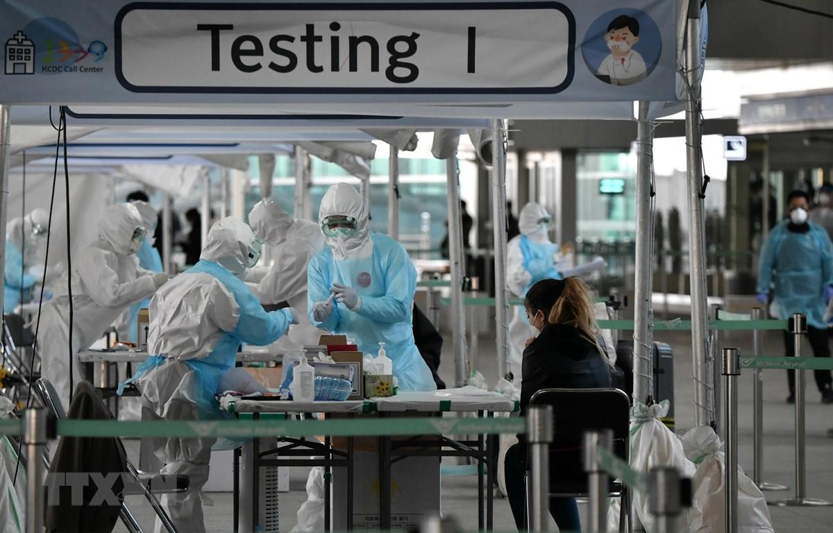 Nhân viên y tế lấy mẫu dịch xét nghiệm COVID-19 cho hành khách tại sân bay quốc tế Incheon, phía tây thủ đô Seoul, Hàn Quốc, ngày 1/4/2020. (Ảnh: AFP/TTXVN)