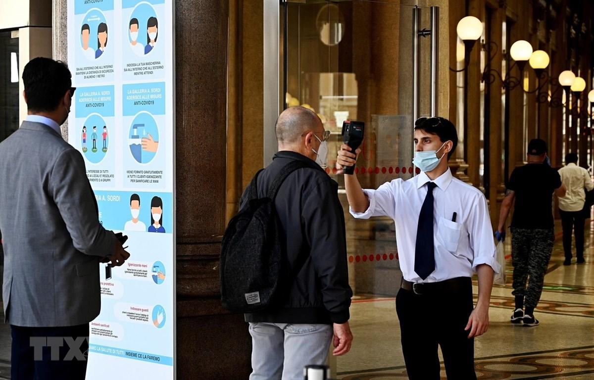 Kiểm tra thân nhiệt phòng lây nhiễm COVID-19 trước khi vào một trung tâm mua sắm ở Rome, Italy. (Ảnh: AFP/TTXVN)