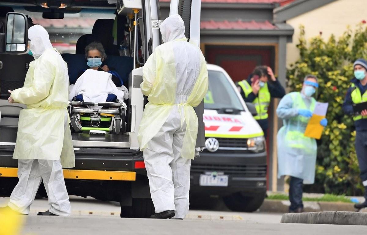 Nhân viên y tế chuyển bệnh nhân nghi mắc COVID-19 lên xe cứu thương tại bang Victoria, Australia ngày 27/7/2020. (Ảnh: AFP/TTXVN)