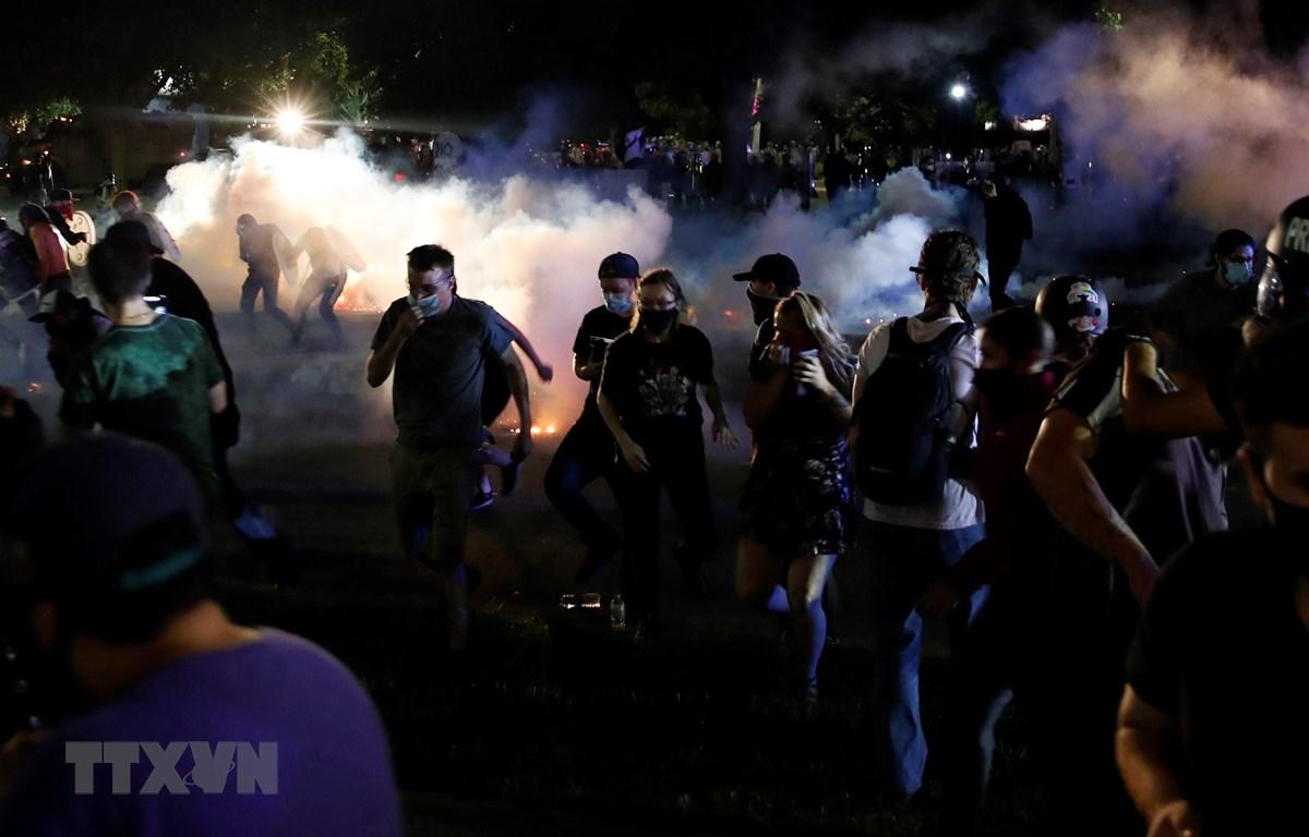 Người biểu tình xung đột với cảnh sát trong cuộc tuần hành phản đối vụ cảnh sát bắn người da màu tại Kenosha, bang Wisconsin (Mỹ) ngày 25/8/2020. (Ảnh: AFP/TTXVN)