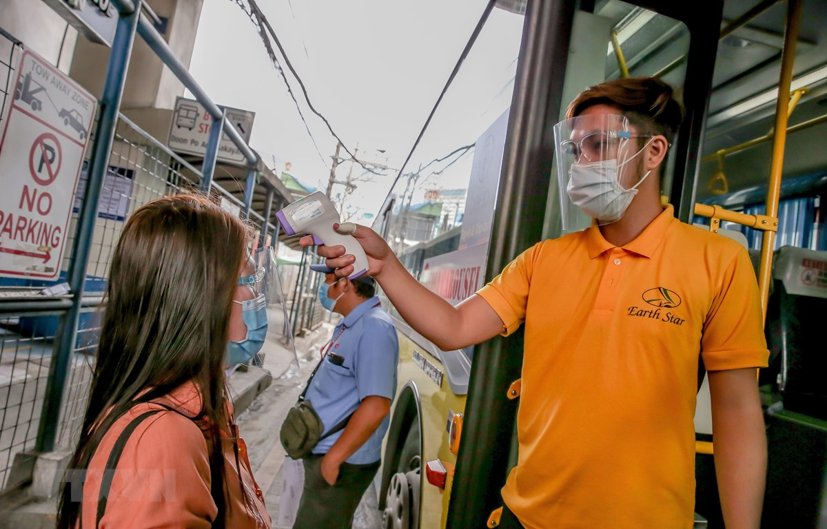 Người dân được kiểm tra thân nhiệt phòng lây nhiễm COVID-19 trước khi lên xe buýt tại Manila, Philippines, ngày 19/8/2020. (Ảnh: THX/TTXVN)