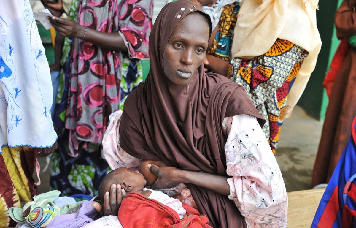 Một bà mẹ mang con bị suy dinh dưỡng tới khám tại bệnh viện ở Gao, Mali. (Ảnh: AFP/TTXVN)