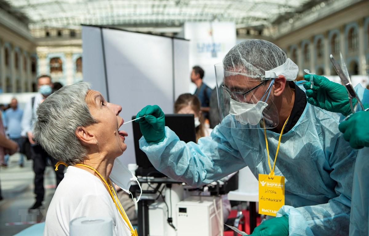 Nhân viên y tế lấy mẫu dịch xét nghiệm COVID-19 cho người dân tại Moskva, Nga, ngày 11/8/2020. (Ảnh: THX/TTXVN)