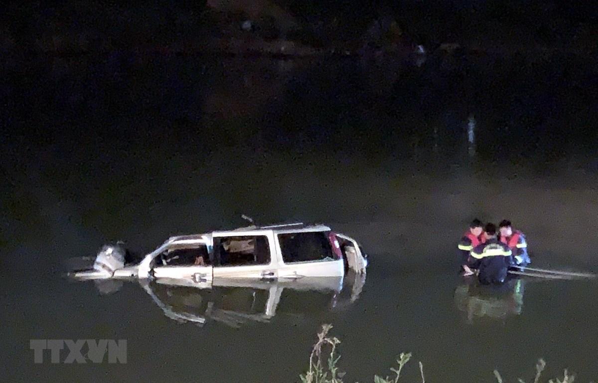 Lực lượng cứu hộ trục vớt chiếc xe ô tô 7 chỗ cùng các thi thể nạn nhân trong đêm. (Ảnh: TTXVN phát)
