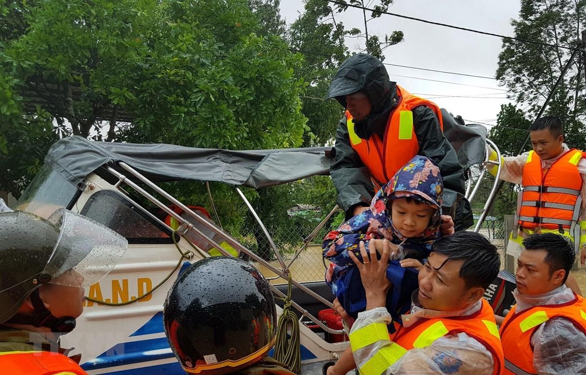 Di chuyển người dân ra khỏi khu vực ngập lũ tại huyện Cam Lộ. (Ảnh: Thanh Thủy/TTXVN)