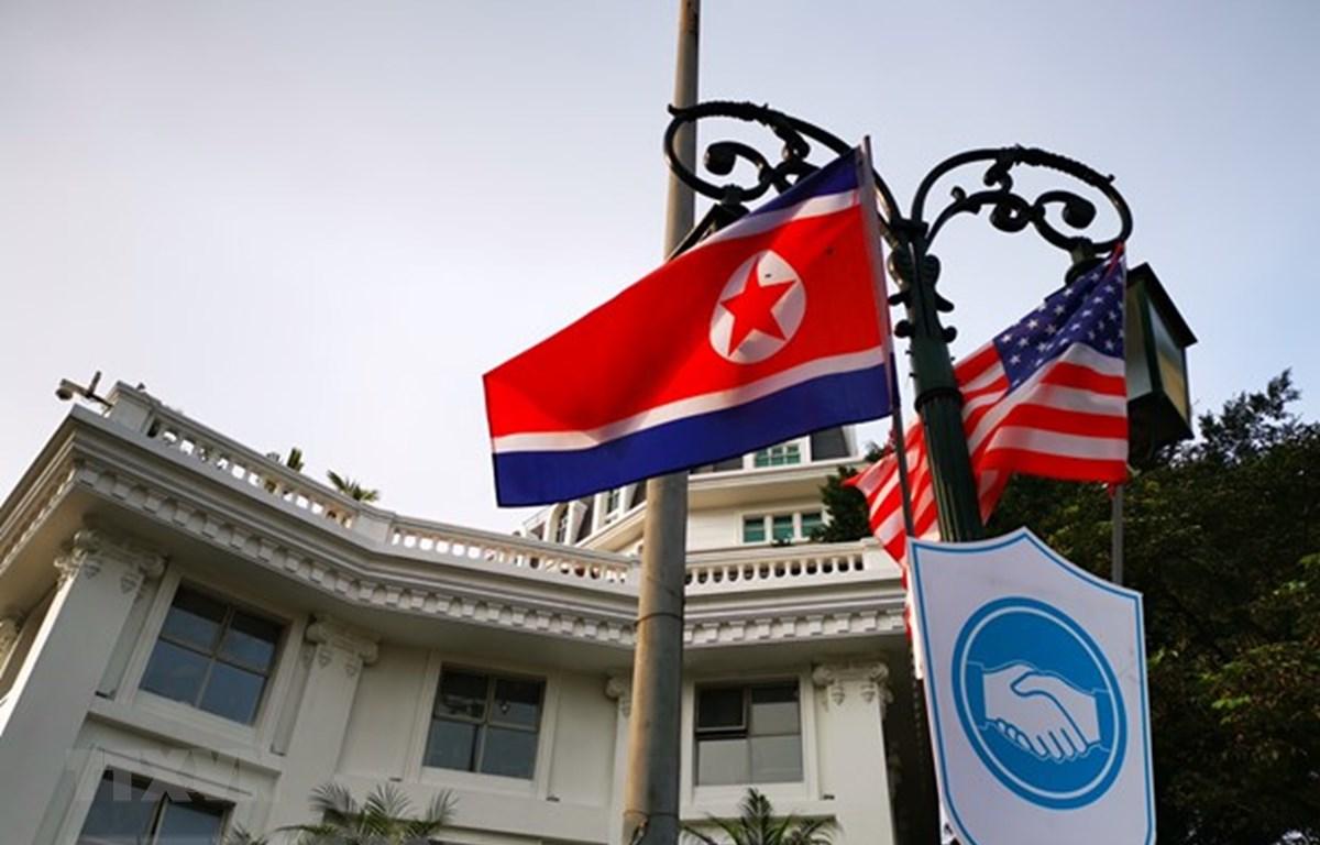 Cờ Mỹ và cờ Triều Tiên, bên dưới là biểu tượng hai bàn tay bắt chặt vào nhau thể hiện tinh thần của cuộc gặp lớn, được treo bên ngoài khu vực Quảng trường 19/8 - Nhà hát Lớn - Khách sạn Hilton Opera, Quận Hoàn Kiếm. (Ảnh: Thành Đạt/TTXVN)